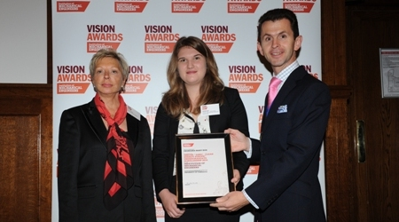 Georgina Box is presented with an award by President Mark Hunt and Barbara Smith from AMEC