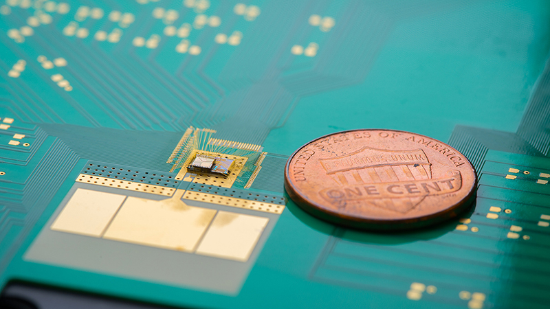 The wake-up receiver, the chip stack to the left of the coin, can cut down on IoT device power use and extend battery life (Credit: David Baillot/ UC San Diego Jacobs School of Engineering)
