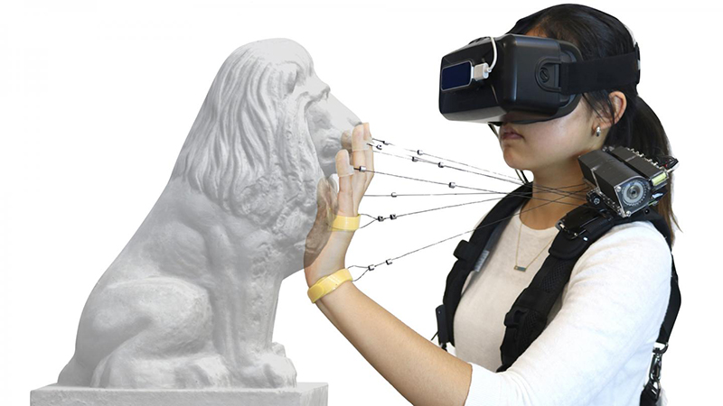 A new device developed at Carnegie Mellon University uses multiple strings attached to the hand and fingers to simulate the feel of obstacles and heavy objects in virtual reality environments (Credit: Carnegie Mellon University)