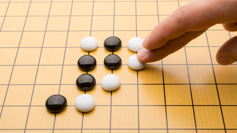 A human player moves a piece during a game of Go (Credit: iStock)