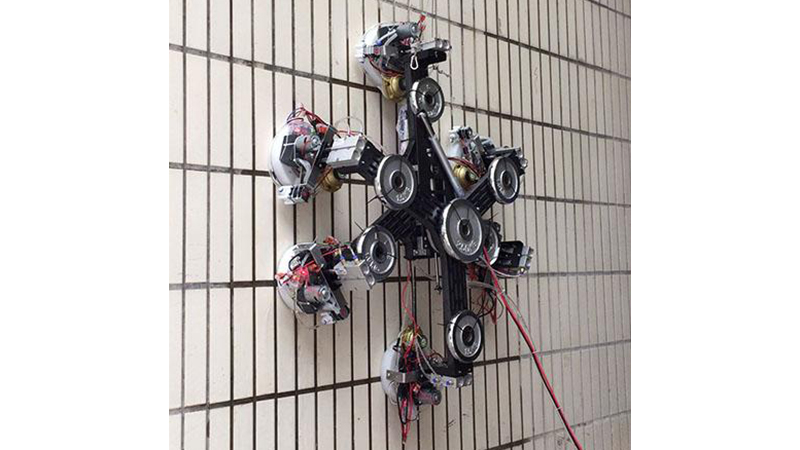 The wall-climbing robot defies gravity on a vertical surface thanks to a new technique developed at the American Institute of Physics (Credit: Xin Li and Kaige Shi)