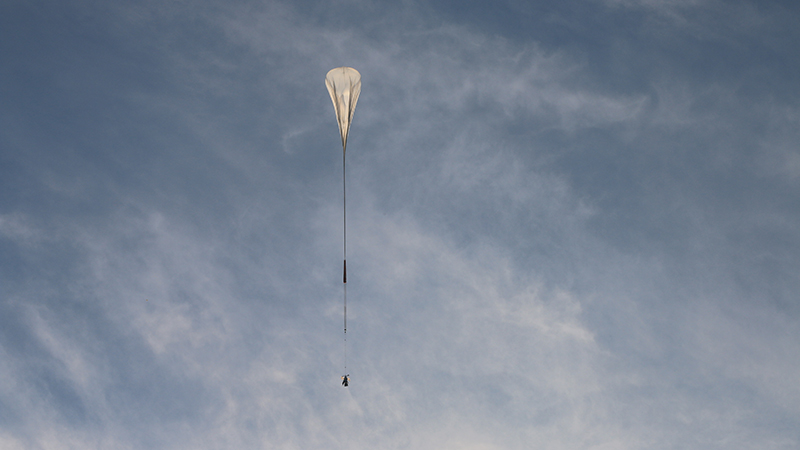 The Superbit telescope in flight, carried by the giant NASA helium balloon
